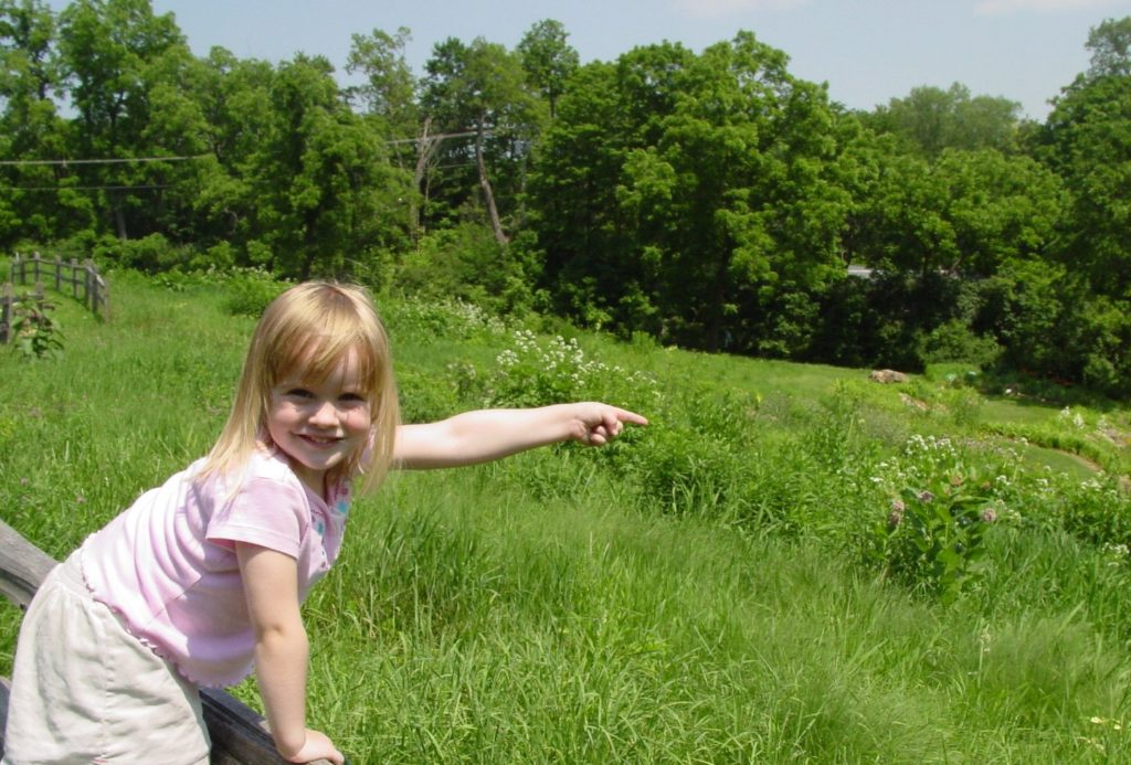 Photo of a girl pointing at the wonders along our nature trails.