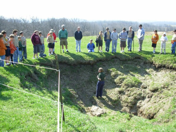 Photo of tour guide in sinkhole teaching scouts about karst typography