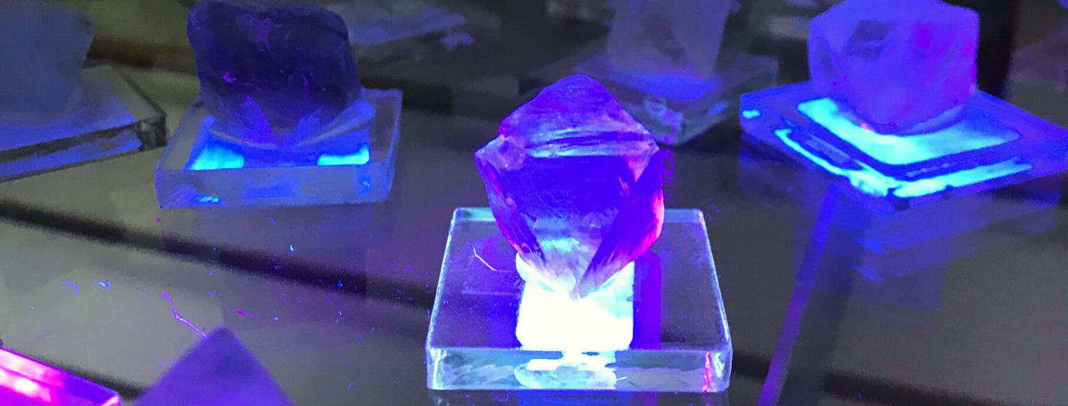 Photo of fluorite glowing under a blacklight