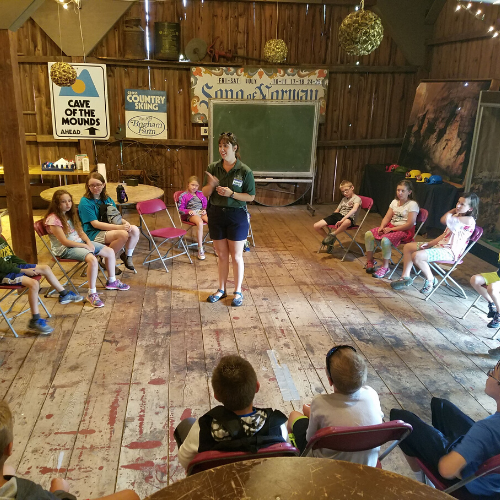Photo of educator surrounded by kids in barn