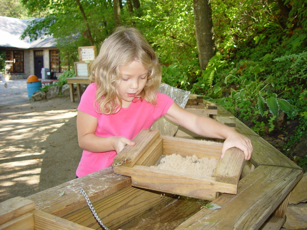 A photo of our Gem Mine with Child sifting through the sand for rocks or fossils.